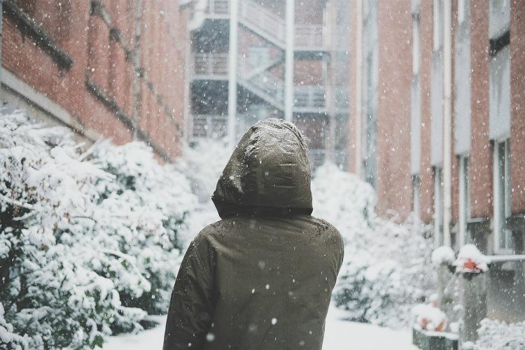 雪が降る寒い日にダウンジャケットを着ている人