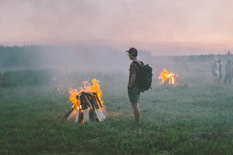 焚火を見つめる男性